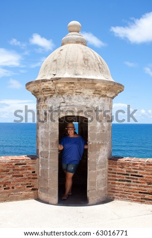 A tourist poses in an old fort watch tower located in Old San Juan Puerto Rico at the historic San Cristobal fortification.