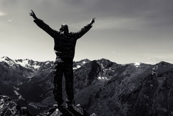 A tourist raised his hands to the sky reveal the joy of conquering the mountain peaks. Standing raised arms man statue. black and white photo