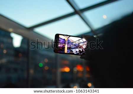 A tourist records video on their cell phone from their cruise boat as evening falls on the Seine River in Paris France