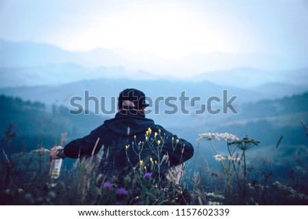A tourist sits and drink alcohol and looks into the distance. Man sit. Wonderful mountain landscape. Summer is time #1157602339