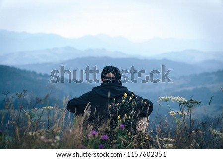 A tourist sits and looks into the distance. Man sit. Wonderful mountain landscape. Summer is time #1157602351