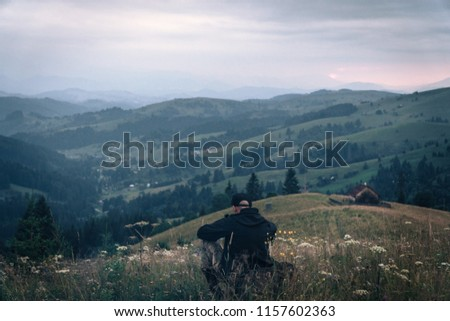 A tourist sits and looks into the distance. Man sit. Wonderful mountain landscape. Summer is time #1157602363