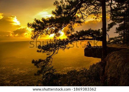 A tourist sitting on Pha Lom Sak on Phu Kradueng at sunset Stock fotó ©