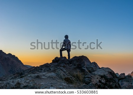 A tourist standing on the peak of a rocky mountain watching sun rising in Darband valley in autumn in dawn against colorful sky in the Tochal mountain.