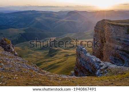 A tourist stands on the cliff edge and looking at sunset on Bermamyt plateau. Karachay-Cherkessia, Caucasus, Russia.