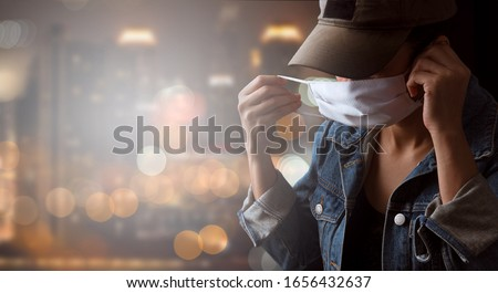 A tourist wearing a mask isolated on city background. Promoting people use face mask to protect themselves from virus infection in Corona virus crisis 2020