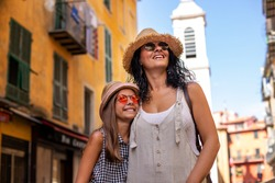 A tourist woman and her daughter walking at the narrow streets of Nice France. Vacation concept with family.
