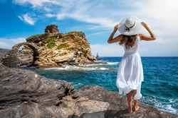 A tourist woman in a white dress stands at the coast of Andros island and enjoys the view to the old stone bridge leading to the ancient castle, Cyclades, Greece