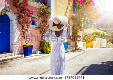 A tourist woman in a white summer dress walks doen the colorful streets of the little village Assos on the island of Kefalonia, Greece Stockfoto ©