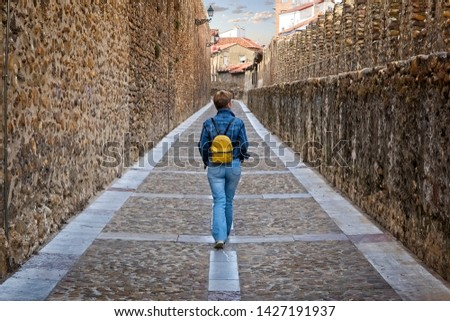 A tourist woman walks through the medieval wall of Leon, Spain