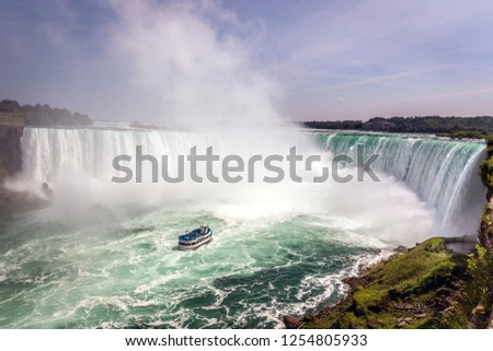 A touristic boat passing very close to a water fall in Niagara Falls in Canada in a blue sky day #1254805933