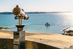 A touristic monocular aiming at the tidal swimming pool of the Bon Secours beach in the old town of Saint-Malo in Brittany, France, from the city wall at sunset.