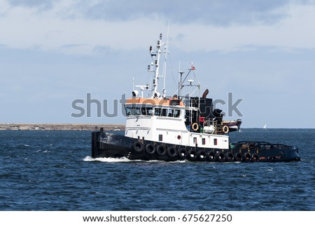 A towboat sails on the sea.