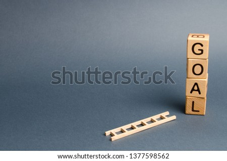 A tower of cubes with an inscription goal and a fallen ladder. Tool for success. Don't give up half way. The concept of achieving the goal, subject to the application of all the efforts and desires.