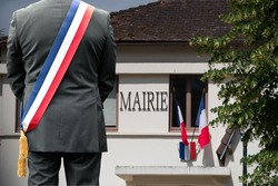 A town hall and the French flag with the mayor in front.