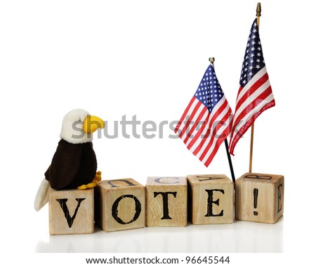 "A toy bald eagle looking at 2 U.S. flags while perched on top of rustic alphabet blocks spelling ""VOTE!"""