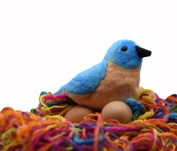 A toy blue and brown bird with a black beak is nesting on two brown eggs on a bird nest made of multi colored yarn reflecting safe keeping of our children and investments