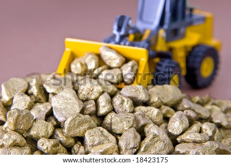 A toy bulldozer moving a pile of gold nuggets.