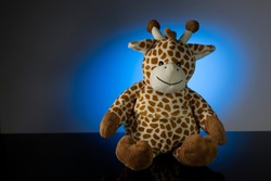 A toy giraffe on a blue background sitting on black glass surface