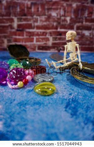 A toy skeleton sits next to treasures. #1517044943