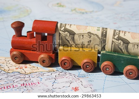 A toy train, loaded with US dollars going to North America.  The concept is trade between nations, international trade.  The map, is in English and Chinese.