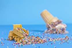 A toy truck pours sprinkles in to a pile with an upturned ice cream cone in the background.