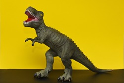 a toy Tyrannosaurus stands on a yellow background