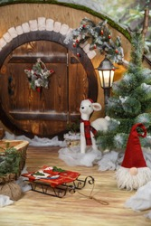 a toy white deer, a wooden stump and a sled on the background of the winter house of the Christmas gnome. studio shot, postcard