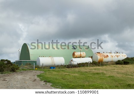 A track leads to a gate with white coloured chemical tanks and a green metal work shed. - stock photo