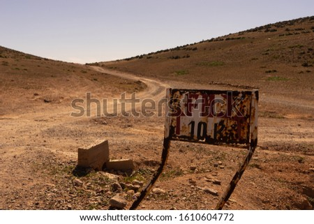 a track to the south near sidi ifni, morocco. the piste leads to the horizon. A street sign leading to fort bou sheriff