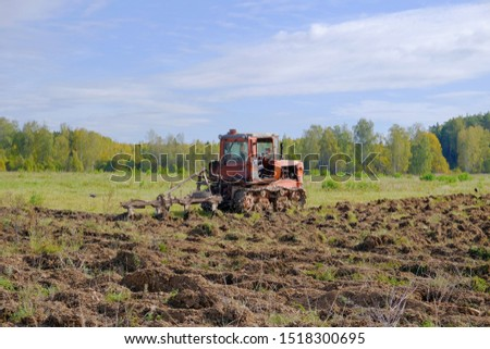 A tracked tractor with a plough plows the ground in autumn against the background of the forest. #1518300695