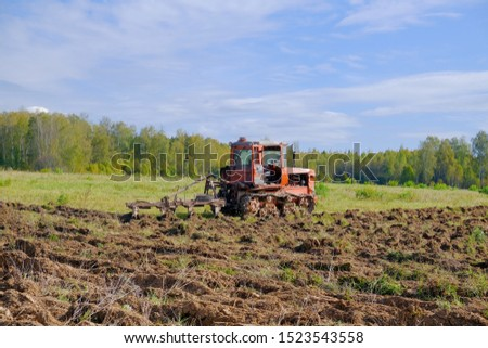 A tracked tractor with a plough plows the ground in autumn against the background of the forest. #1523543558