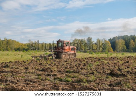 A tracked tractor with a plough plows the ground in autumn against the background of the forest. #1527275831
