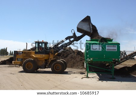 a tractor dumps a pile of mulch into a mulching machine