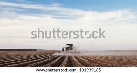 A tractor planting a potato crop on the prairies.