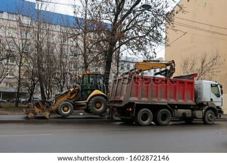 a tractor raised on pylons above the ground loading a heavy truck