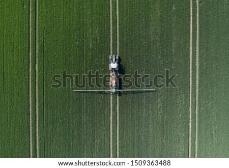 Photo of  A Tractor Spraying Controversial Glyphosate Herbicide onto Farmland Aerial View