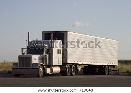 A tractor-trailer truck in a parking lot.
