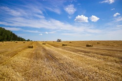 A tractor uses a trailed bale machine to collect straw in the field and make round large bales. Agricultural work, baling, baler, hay collection in the summer field. Agricultural work concept.