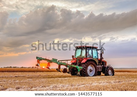 A tractor with a plow. Plowing the field after harvest .