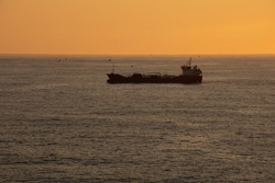 A trade cargo ship sailing alone at the sea in the Atlantic Ocean during sunset. High quality photo