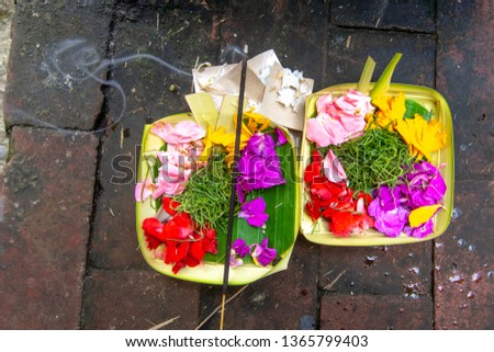 A traditional Balinese Hindu offering with burning incense, offered as a sacrifice to the gods. #1365799403