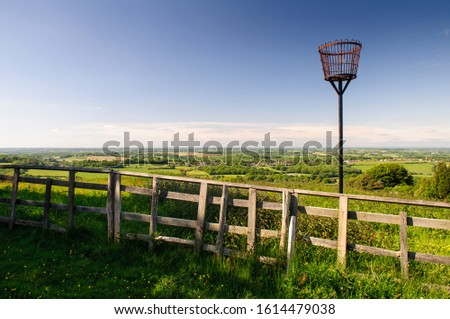 A traditional beacon basket stands in a field on Battery Hill in Fairlight abover the farmland countryside of East Sussex.