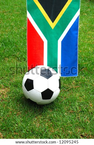 A traditional black and white football in front of the national flag of South Africa on green grass background. South Africa is the official host of the FIFA soccer world cup in 2010.