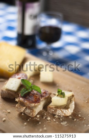 A traditional blue table with a plate with cheese and salami tapas and wine from Portugal