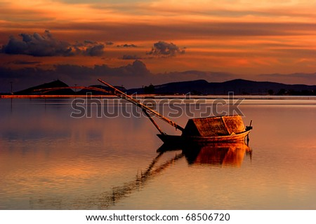 """A traditional boat of the lakes (called """"gaita"""" in greek) in the lagoon of Messolonghi, around sunset"""