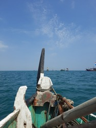 A Traditional Boat Sails in Java Sea at Morning with Beautiful Blue Sky and Water Scape as Background