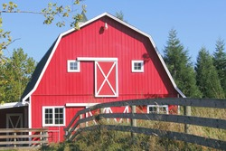 A traditional bright red barn with a white picket fence/Traditional Red Barn/A traditional North American red barn with a white picket fence.
