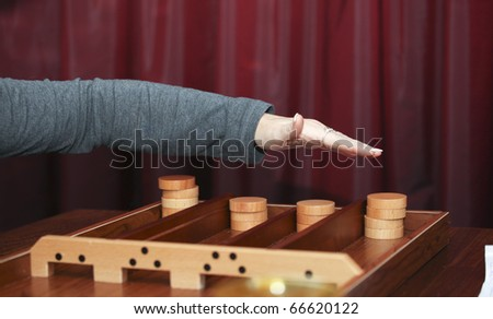 A traditional Dutch game called 'sjoelen'. You have to slide the wooden disks in the holes at the far end.