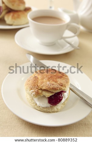 A traditional English cream tea, with scones, strawberry jam and whipped cream, served with tea and milk
